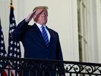 FILE PHOTO: U.S. President Donald Trump salutes as he poses without a face mask on the Truman Balcony of the White House after returning from being hospitalized at Walter Reed Medical Center for coronavirus disease (COVID-19) treatment, in Washington, U.S. October 5, 2020. REUTERS/Erin Scott/File Photo