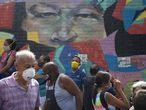 Pedestrians wearing protective face masks as a precaution against the spread of COVID-19, walk past a mural featuring the eyes of the late President Hugo Chavez, in Caracas, Venezuela, Thursday, July 2, 2020. Part of Venezuela is under strict quarantine as the number of infected cases continue to rise amid the pandemic. (AP Photo/Ariana Cubillos)