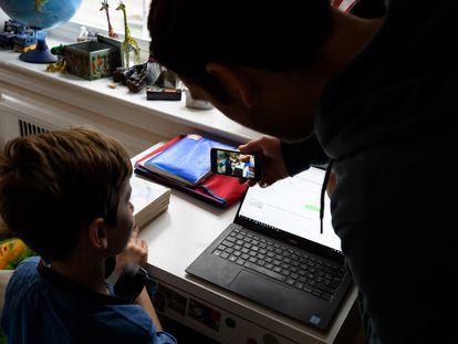 Menino grava mensagem para seus amigos no celular de seu pai em Washington, nesta sexta-feira.