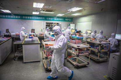 Funcionários de uma empresa chinesa que fabrica exames de diagnóstico para o coronavírus.