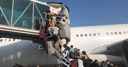 Afegãos tentam acessar um avião no aeroporto de Cabul na segunda-feira.