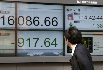 Empresários caminham junto a telas que mostram informação da Bolsa em Tóquio.