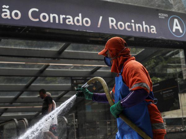 BRA01. RIO DE JANEIRO (BRASIL), 09/04/20.- Un empleado de la Compañía de Limpieza Urbana (COMLURB) limpia este jueves las calles de la entrada de la favela de Rocinha, una barriada con 69.161 habitantes en solo 865.032 metros cuadrados, en la zona sur de Río de Janeiro (Brasil). EFE/Antonio Lacerda