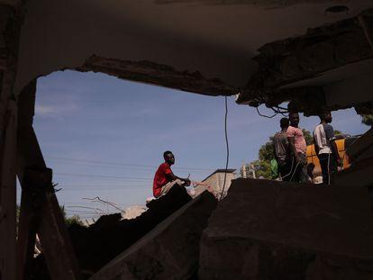 Um grupo de pessoas remove escombros em uma rua de Los Cayos