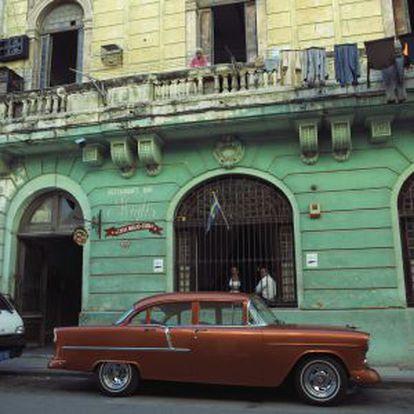 Um carro antigo e o restaurante Casa Miglis.