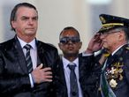 (FILES) In this file photo taken on April 17, 2019 Brazilian President Jair Bolsonaro (L) and Army Commander Edson Pujol are drenched with rain as they attend a ceremony to mark Army Day, in Brasilia, two days ahead of the actual celebration date. - The commanders of Brazil's army, navy and air force will be replaced, the government said Tuesday, a day after President Jair Bolsonaro overhauled his cabinet with six substitutions, including a new defense minister. (Photo by Sergio LIMA / AFP)