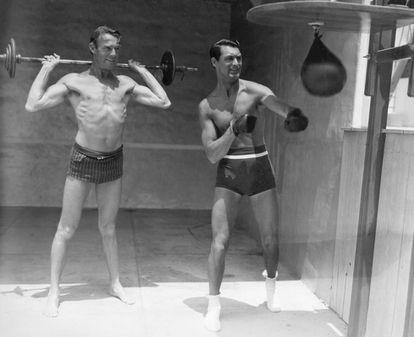 Cary Grant e Randolph Scott fazem ginástica juntos.