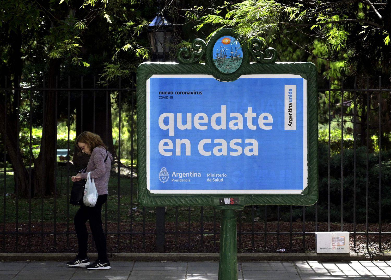 Mulher passa diante de um cartaz do Governo pedindo à população que não saia às ruas como prevenção contra o coronavírus.