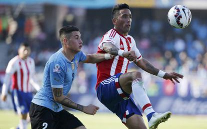 José Giménez, do Uruguai, marca o atacante paraguaio Lucas Barrios.