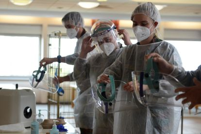 Profissionais médicos usam protetores faciais para receber pacientes com coronavírus, em Seraing, Bélgica.