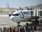 Un grupo de ciudadanos afganos se suben a uno de los aviones del aeropuerto de Kabul.