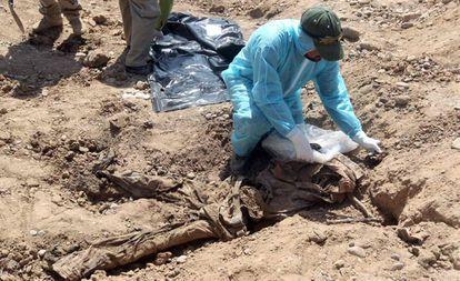 Um membro das forças de segurança iraquianas examina os restos de uma pessoa em uma vala comum em Tikrit, em abril de 2015.