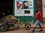 A man wearing a face mask walks near a sign depicting Cuban late leader Fidel Castro and reading �Revolution is to change everything that needs to be changed�, in Havana on May 13, 2020, amid the new coronavirus pandemic. - Cuba has confirmed 1,810 cases of COVID-19, from which 79 have died. (Photo by YAMIL LAGE / AFP)
