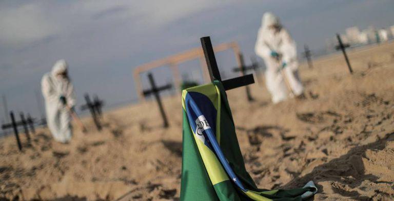 Ativistas colocam cruzes na praia de Copacanbana para criticar o manejo da crise pelo Governo durante manifestação em junho.
