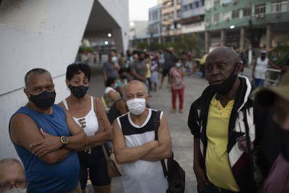 Pessoas aguardam na fila sua dose da Coronavac em Duque de Caxias, Rio de Janeiro, nesta quarta-feira.