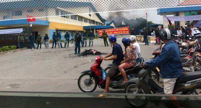 Motociclistas passam por policiais que vigiam a área onde se encontra uma fábrica incendiada na província vietnamita de Binh Duong.