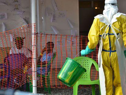 Funcionário da saúde com pacientes em quarentena em agosto na Guiné.