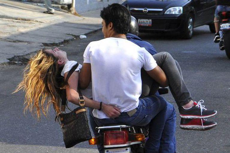 Genesis Carmona é levada em uma moto depois de ser atingida por um tiro.