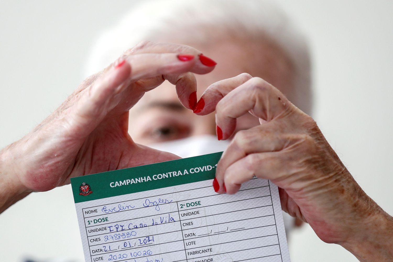 Uma idosa faz o formato de um coração com as mãos ao mostrar o atestado de vacinação contra covid-19 em São Paulo.