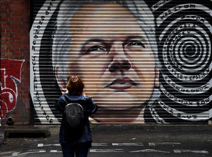 Mulher fotografa muro com imagem de Julian Assange em Melbourne, na Austrália, nesta terça.