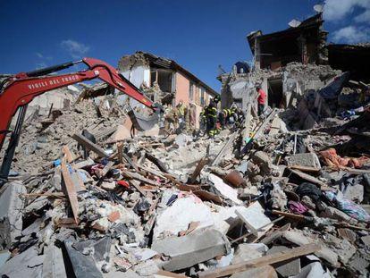 Os bombeiros e as equipes de resgata inspecionam edifícios destruídos em Amatrice.