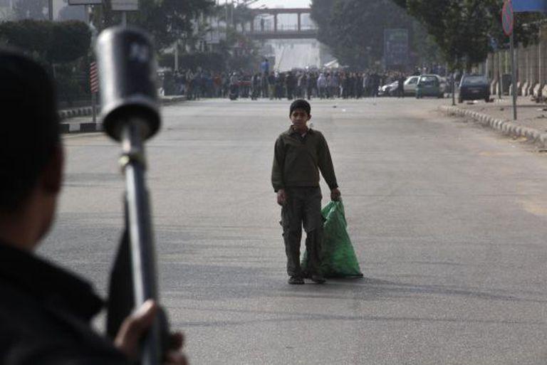Uma criança observa membros das forças de segurança do Egito que estão dispostos a dissolver uma manifestação de apoio a Mursi, na sexta-feira.