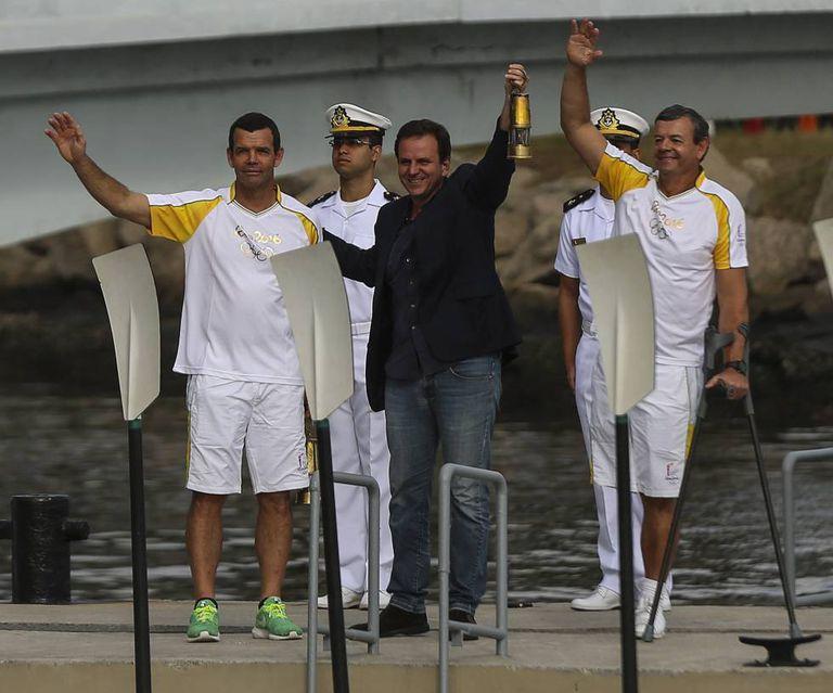 O prefeito Eduardo Paes recebe dos medalhistas olímpicos Torben (à esq.) e Lars Grael a tocha olímpica.