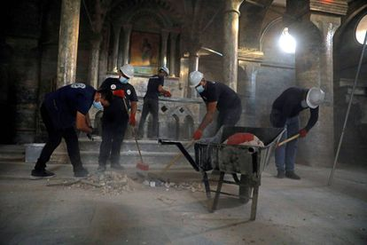 Grupo de voluntários trabalha para limpar a igreja de São Tomás em Mosul (Iraque), profanada pelo Estado Islâmico.