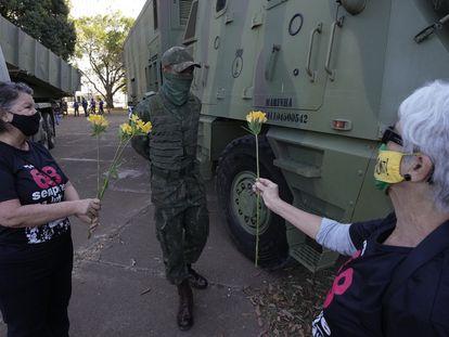 Duas militantes que fizeram oposição à ditadura brasileira oferecem flores a militar, em Brasília.