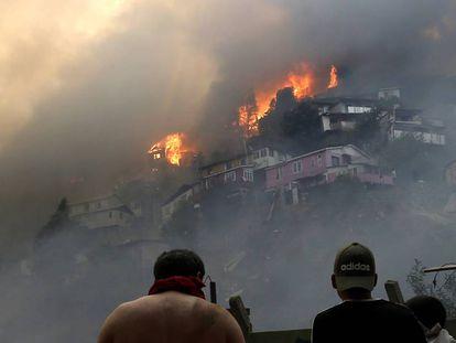 Vários homens contemplam o incêndio na serra Rocuant, de Valparaíso, na noite de terça-feira.