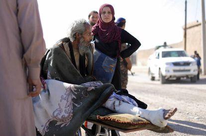 Um homem ferido em uma maca foge de Raqqa nesta terça-feira.