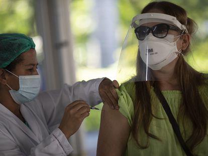 Mulher é vacinada no Rio.