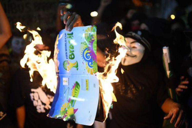 Manifestante queima álbum da Copa.