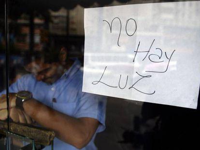 Empregado atrás da porta de uma loja fechada em Caracas.