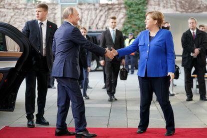 O presidente russo, Vladimir Putin, e a chanceler alemã, Angela Merkel, cumprimentam-se em Berlim, em janeiro de 2020, no início de uma conferência sobre a Líbia.