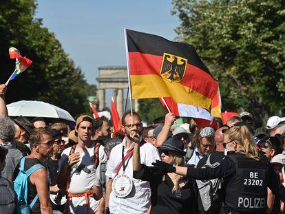 Policial se dirige aos manifestantes em Berlim neste sábado, que reuniu 15.000 pessoas.
