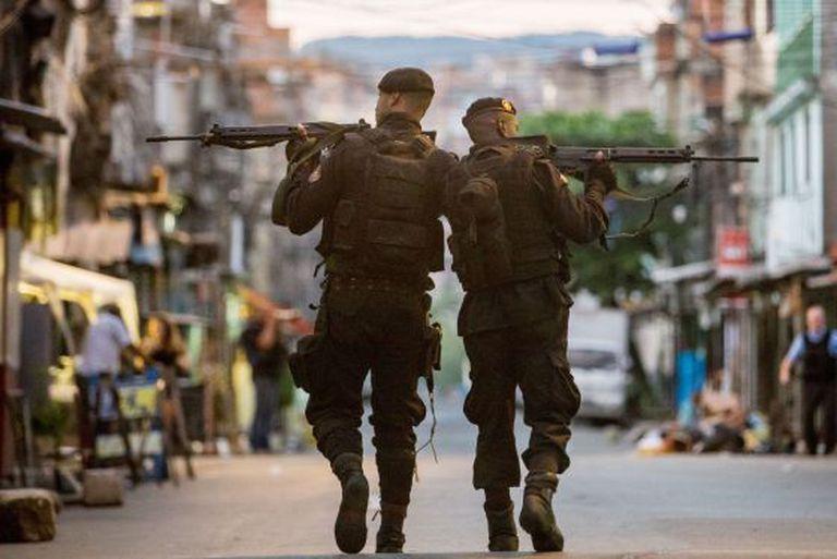 Policiais do BOPE patrulham as ruas das favelas da Maré.