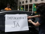 """A woman attaches a sign reading """"impeachment now"""" during a motorcade to protest against Brazil's President Jair Bolsonaro and his handling of the coronavirus disease (COVID-19) outbreak in Sao Paulo, Brazil January 24, 2021. REUTERS/Amanda Perobelli"""
