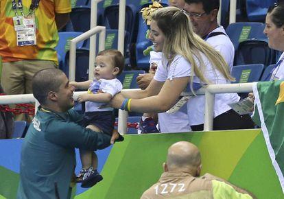 A mulher de Daniel, Raquel, entrega o filho menos para o nadador após a prova.