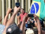 Brazilian President Jair Bolsonaro speaks after joining his supporters who were taking part in a motorcade to protest against quarantine and social distancing measures to combat the new coronavirus outbreak in Brasilia on April 19, 2020. (Photo by EVARISTO SA / AFP)