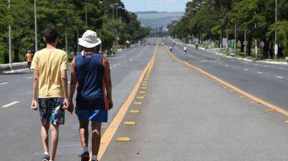 Pessoas caminham pelo Eixão, em Brasília.