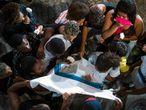 Amigos e familiares de Marcos Vinícios choram sobre sua camiseta da escola manchada de sangue, nesta quinta-feira.