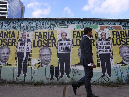 Homem passa diante de cartazes do ministro da Economia, Paulo Guedes, em São Paulo no dia 30 de agosto.