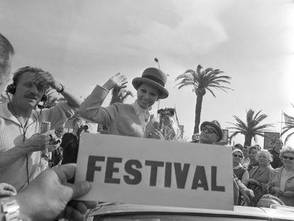 A atriz italiana Sophia Loren acena para a multidão no Festival do ano de 1964, acompanhada do seu marido, Carlo Ponti (à dir.), e do presidente do Festival de Cannes, Favre Le Bret (à esq.).
