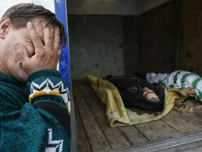 Um vizinho de Slaviansk chora diante de dois cadáveres depois do combate da madrugada do domingo em um posto de controle.