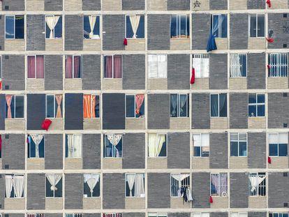 Edifício no centro de Bogotá onde janelas exibem panos vermelhos como pedido de ajuda.
