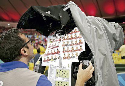 Um operador de câmera brasileiro acompanha o jogo entre Espanha e Chile na Copa do Mundo de 2014 com os mapas das posições dos jogadores sobre o campo. Mesmo na era digital, os profissionais ainda preferem usar folhas de papel presas com fita adesiva para controlar quem faz cada jogada.