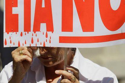 Uma mulher chora com um cartaz escrito
