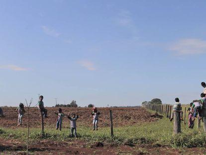 Estudantes da escola indígena da aldeia Guyraroká brincam na cerca com a fazenda vizinha da comunidade.