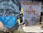 A man walks past a graffiti by Mathare Roots's youth group, which advocates against the spread of the coronavirus disease (COVID-19), at the Mathare Valley slum, in Nairobi, Kenya April 19, 2020. Picture taken April 19, 2020. REUTERS/Thomas Mukoya
